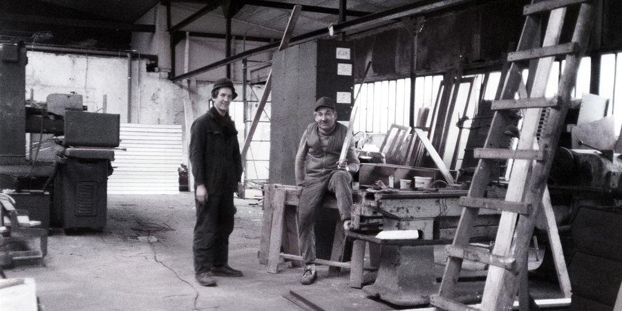 Two employees sitting and standing in a modern production hall shown in black and white surrounded by practical tools for all kinds of tasks.