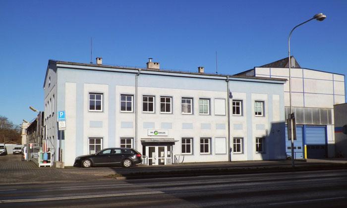 Internationale Produktionsstätte in Tschechien für europäische Baumaschinenproduktion, an der Straße gelegen mit äußerlichen blauen und weißen Farbtönen.