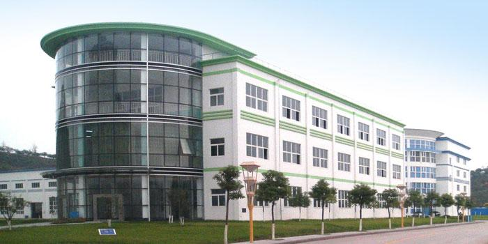 Exterior view of the green and white, large and multi-storey building with glass front and row of trees by the international Dr. Schulze GmbH.