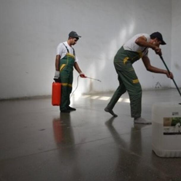 Zwei Arbeiter sind zu sehen die mittels Sprühfalsche das DRS-FLOOR HDS+ Betonvergütungsmittel auf den Boden für exzellente Resultate auftragen.
